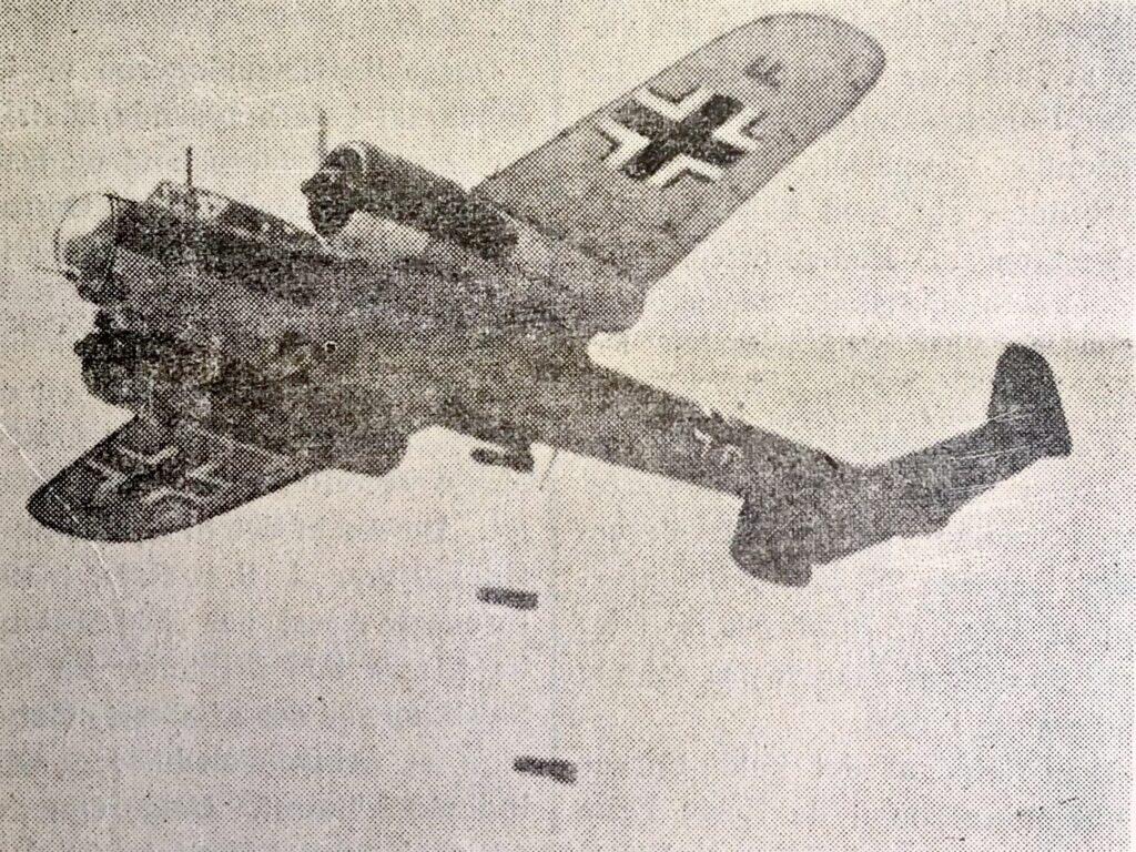 En tysk flyver fotograferet mens den kaster bomber ned over fronten. Billede bragt i Kolding Socialdemokrat, 15. juni 1940, digital udgave af krigendagfordag.dk